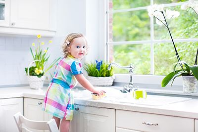 Young girl cleaning the kitchen